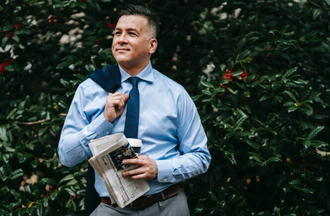 Mand smiler på gaden og holder avis