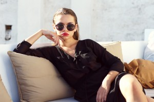 young beautiful woman in black clothes sitting on sofa outdoors in summer