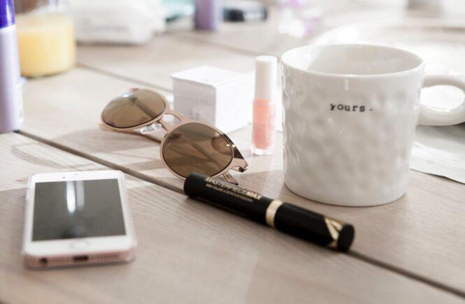 Solbriller og telefon ligger på bord
