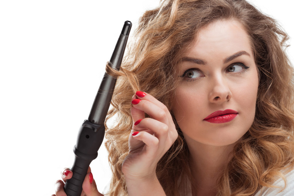 Ung kvinde krøller håret med et krøllejern